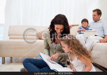 Mother showing photo album to daughter stock photo, Mother showing photo album to her daughter by Wavebreak Media