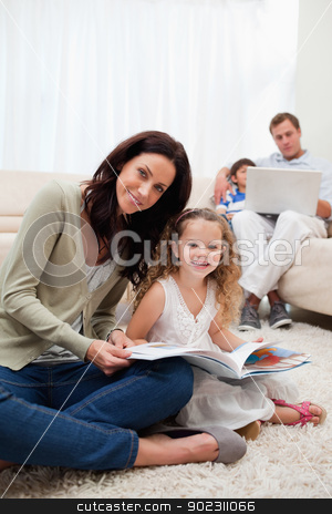 Mother and daughter reading book together stock photo, Mother and daughter reading book in together in the living room by Wavebreak Media