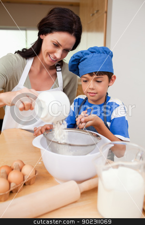 Mother and son preparing dough stock photo, Mother and son preparing dough together by Wavebreak Media