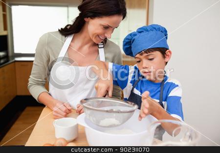 Son and mother preparing dough stock photo, Son and mother preparing dough together by Wavebreak Media