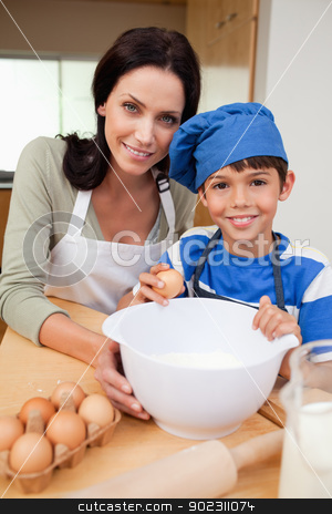 Son and mother baking cake stock photo, Son and mother baking cake together by Wavebreak Media