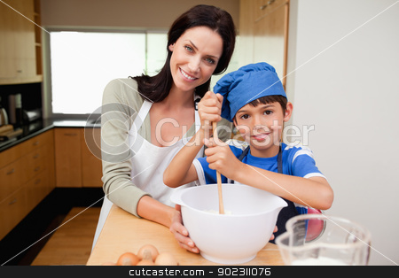 Mother and son having fun preparing dough stock photo, Mother and son having fun preparing dough together by Wavebreak Media