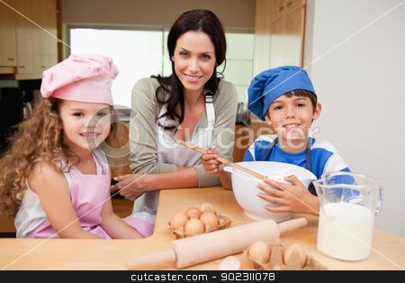 Mother and her children preparing cake stock photo, Mother and her children preparing cake together by Wavebreak Media