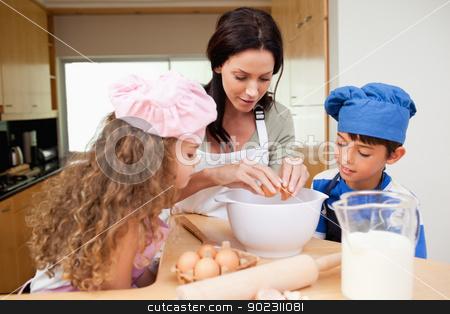 Mother making cookies with her kids stock photo, Mother making cookies together with her kids by Wavebreak Media