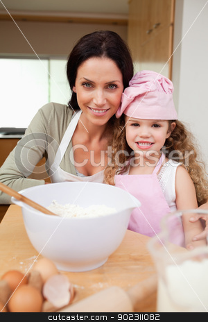 Mother and daughter preparing cake stock photo, Mother and daughter preparing cake together by Wavebreak Media