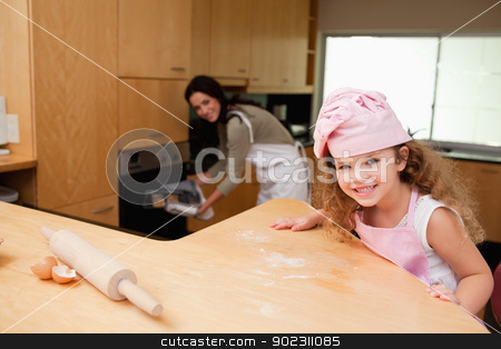 Girl sitting in the kitchen while her mother puts cookies into t stock photo, Young girl sitting in the kitchen while her mother puts cookies into the oven by Wavebreak Media