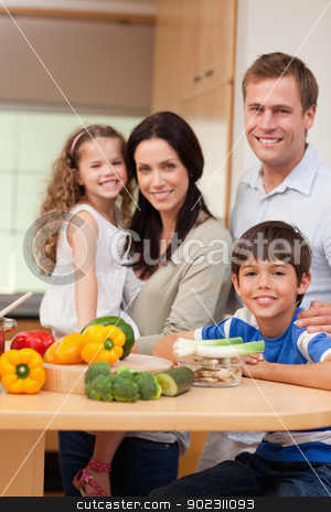 Young family standing in the kitchen stock photo, Young family standing in the kitchen together by Wavebreak Media