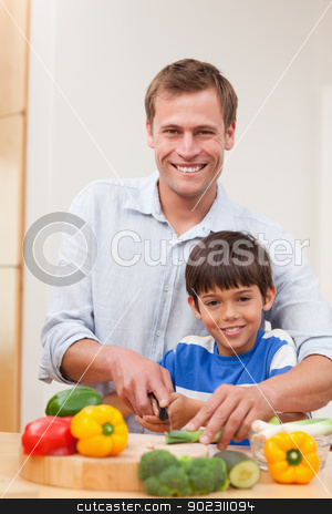 Father and son cutting vegetables stock photo, Father and son cutting vegetables together by Wavebreak Media