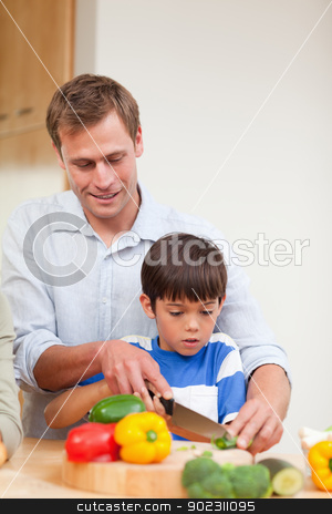 Father and son slicing vegetables stock photo, Father and son slicing vegetables together by Wavebreak Media