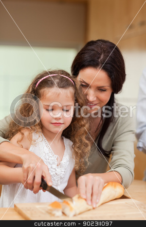 Mother and daughter cutting bread into slices stock photo, Mother and daughter cutting bread into slices together by Wavebreak Media