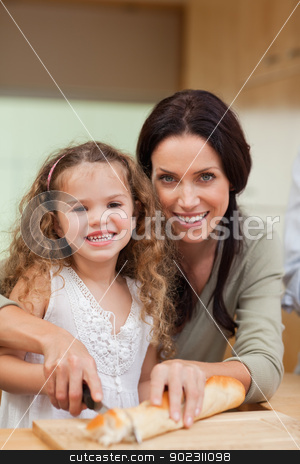 Mother and daughter slicing bread stock photo, Mother and daughter slicing bread together by Wavebreak Media
