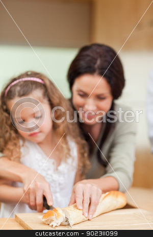 Mother and daughter cutting bread stock photo, Mother and daughter cutting bread together by Wavebreak Media