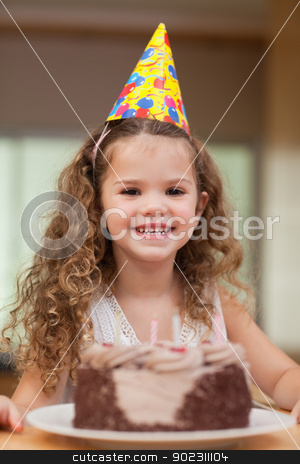 Girl with a slice of cake in front of her stock photo, Smiling girl with a slice of cake in front of her by Wavebreak Media