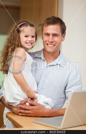 Father showing laptop to his daughter stock photo, Young father showing laptop to his daughter by Wavebreak Media
