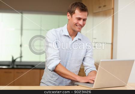 Man working on laptop in the kitchen stock photo, Smiling man working on laptop in the kitchen by Wavebreak Media