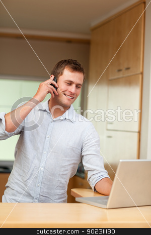 Male with cellphone and laptop in the kitchen stock photo, Smiling male with cellphone and laptop in the kitchen by Wavebreak Media