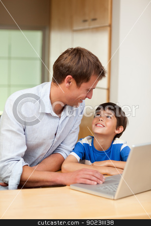 Father and son with laptop stock photo, Father and son with laptop in the kitchen by Wavebreak Media