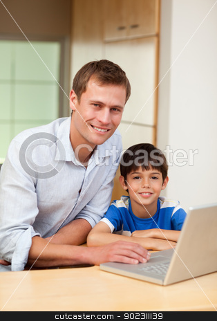 Father and son with notebook stock photo, Father and son with notebook in the kitchen by Wavebreak Media
