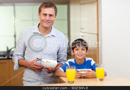 Father and son having cereals and orange juice stock photo, Father and son having cereals and orange juice together by Wavebreak Media