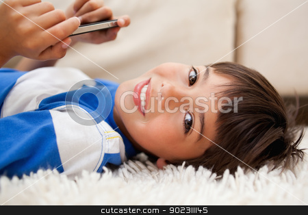 Boy lying on the carpet with cellphone stock photo, Little boy lying on the carpet with cellphone by Wavebreak Media