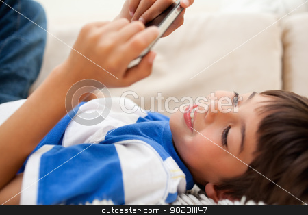 Boy lying on the carpet playing with his cellphone stock photo, Little boy lying on the carpet playing with his cellphone by Wavebreak Media