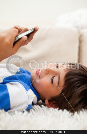 Boy playing with his cellphone while lying on the carpet stock photo, Little boy playing with his cellphone while lying on the carpet by Wavebreak Media