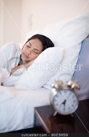 Side view of woman sleeping in her bed stock photo, Side view of young woman sleeping in her bed by Wavebreak Media