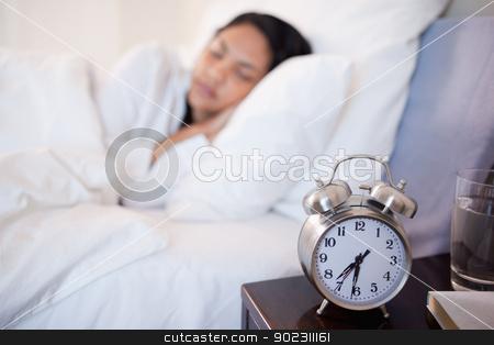 Alarm clock next to woman sleeping in her bed stock photo, Alarm clock next to young woman sleeping in her bed by Wavebreak Media