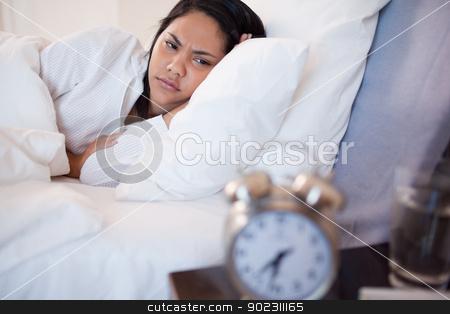 Side view of woman being woken by alarm clock stock photo, Side view of young woman being woken by alarm clock by Wavebreak Media