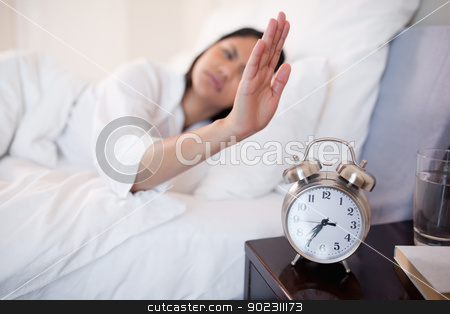 Alarm clock being turned off by woman stock photo, Alarm clock being turned off by young woman by Wavebreak Media