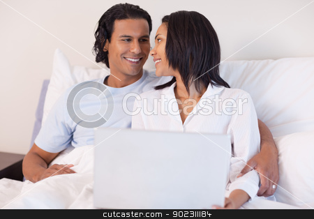 Young couple sitting on the bed with their laptop stock photo, Smiling young couple sitting on the bed with their laptop by Wavebreak Media