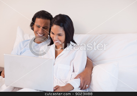 Couple sitting on the bed using the internet stock photo, Young couple sitting on the bed using the internet by Wavebreak Media