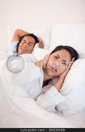 Woman being annoyed by snoring boyfriend stock photo, Young woman being annoyed by snoring boyfriend by Wavebreak Media