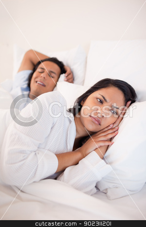 Displeased woman lying next to snoring boyfriend stock photo, Displeased young woman lying next to snoring boyfriend by Wavebreak Media