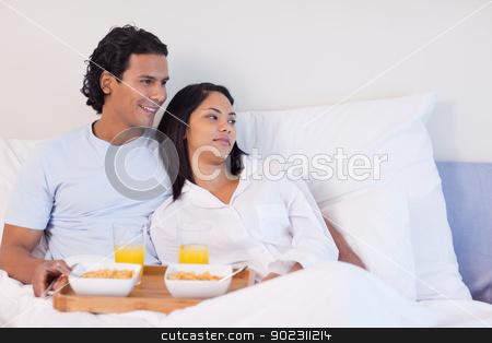 Couple having breakfast in the bed stock photo, Young couple having breakfast in the bed by Wavebreak Media