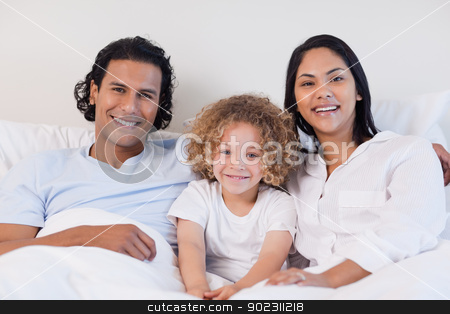 Happy family sitting on the bed together stock photo, Happy young family sitting on the bed together by Wavebreak Media