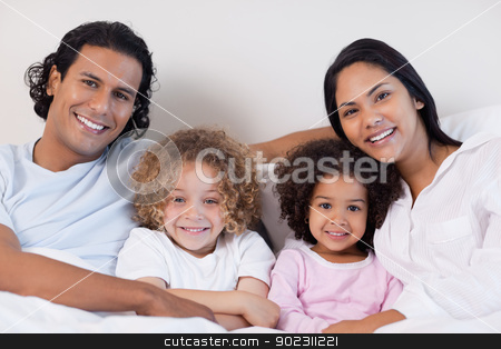 Smiling family sitting on the bed together stock photo, Happy smiling family sitting on the bed together by Wavebreak Media