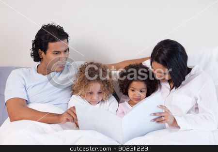 Parents reading a book with their children stock photo, Young parents reading a book with their children by Wavebreak Media