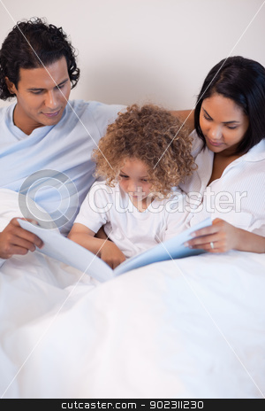 Family sitting on the bed reading a story stock photo, Young family sitting on the bed reading a story by Wavebreak Media