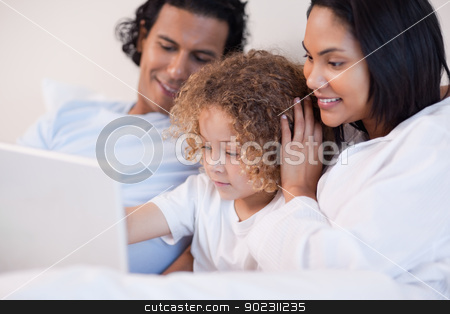 Family sitting on the bed with laptop together stock photo, Young family sitting on the bed with laptop together by Wavebreak Media