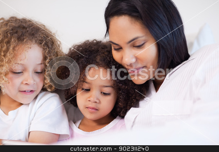 Woman sitting on the bed with her daughters stock photo, Young woman sitting on the bed with her daughters by Wavebreak Media