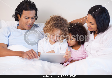 Family sitting on the bed using tablet stock photo, Young family sitting on the bed using tablet by Wavebreak Media