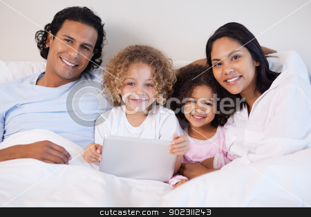 Family together on the bed with laptop stock photo, Young family together on the bed with laptop by Wavebreak Media
