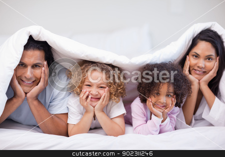 Family hiding under the bed cover stock photo, Young family hiding under the bed cover by Wavebreak Media