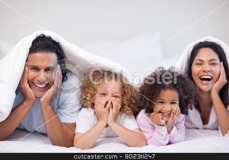 Joyful family hiding under the blanket stock photo, Joyful young family hiding under the blanket by Wavebreak Media