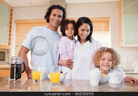 Happy family having breakfast in the kitchen together stock photo, Happy young family having breakfast in the kitchen together by Wavebreak Media