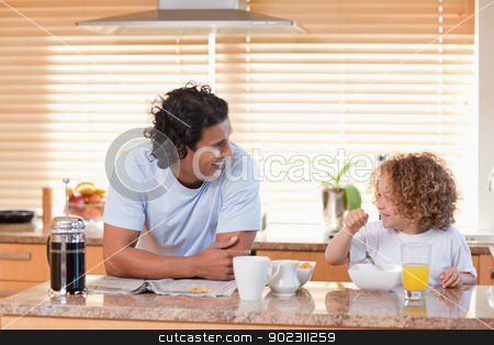 Father and daughter having breakfast in the kitchen stock photo, Young father and daughter having breakfast in the kitchen by Wavebreak Media