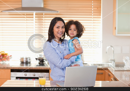 Mother and daughter with notebook in the kitchen together stock photo, Young mother and daughter with notebook in the kitchen together by Wavebreak Media