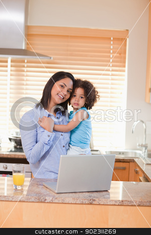 Mother and daughter with laptop in the kitchen stock photo, Young mother and daughter with laptop in the kitchen by Wavebreak Media
