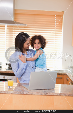 Mother and daughter with notebook in the kitchen stock photo, Young mother and daughter with notebook in the kitchen by Wavebreak Media